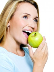 A woman takes a bite out of an apple.