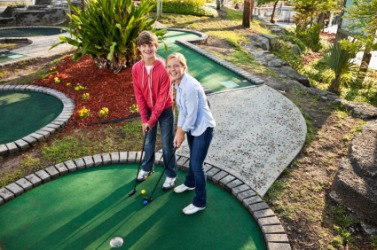 Teenagers playing miniature golf.