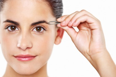 A woman uses tweezers to pluck her eyebrows.