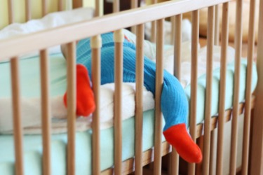 A sleeping baby in his crib.