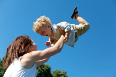 A mother lifts her child into the air.