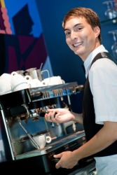 A young barista making coffee.