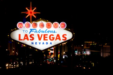 Las Vegas at night seen behind the city sign.