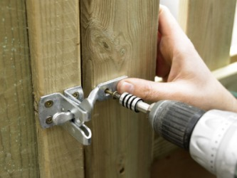 A latch being installed to a gate.
