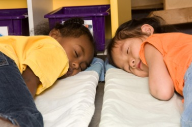 Two children taking a nap at preschool.