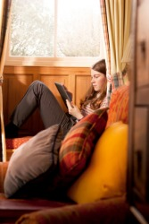 A girl sits reading in a neuk.