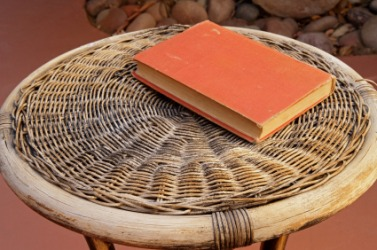 A book sits on this wicker table.