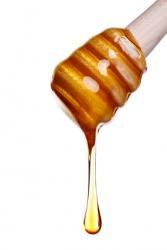 Honey oozes frmo a dipper.