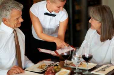 A waiter assists a couple with their restaurant order.