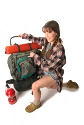 A girl packs for a hiking trip.