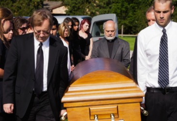 Pallbearers carry a coffin at a funeral.