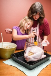A child helping her mother to baste a turkey.