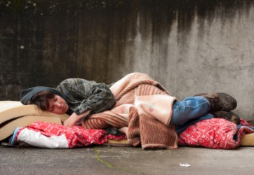 A pauper sleeps on the street.