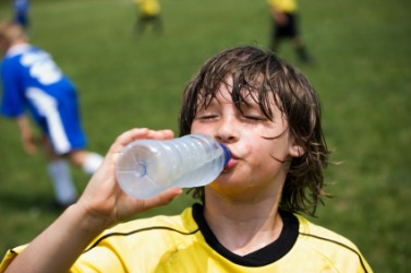 A boy quenches his thirst on a warm day.