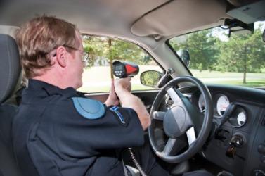 A policeman using a radar gun.