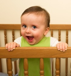A cute baby holding the rail of his crib.