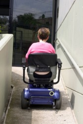 A woman using a wheelchair ramp.