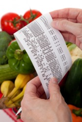 A woman holds a grocery receipt.