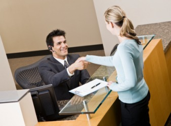 A receptionist greets a businesswoman.
