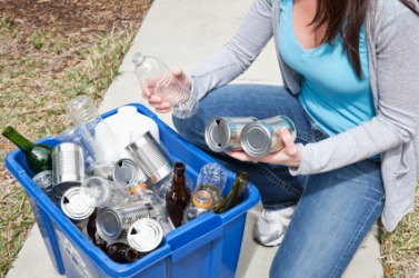 A woman recycles her glass and cans.