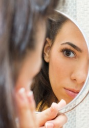 A woman looks at her reflection in a mirror.