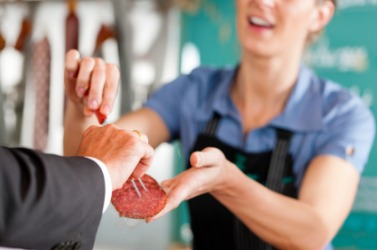 A man gets a sample of sausage at a butchers shop.