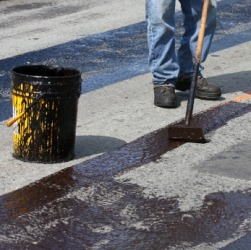 A man spreading hot tar on a road.