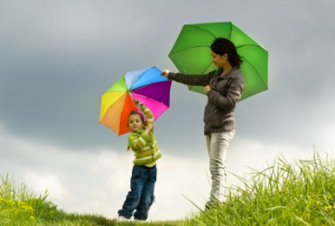 A mother and daughter each carrying an umbrella.