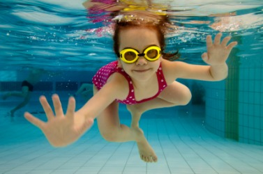 A little girl swims underwater.