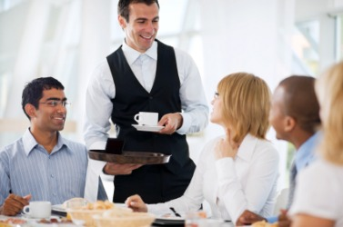 A waiter brings coffee to his customers.