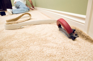 A man installing wall-to-wall carpeting.