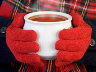 A girl uses a cup of soup to warm her hands.