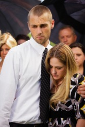 A couple weep at a funeral.