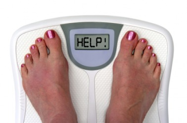 A woman weighs herself on her bathroom scales.