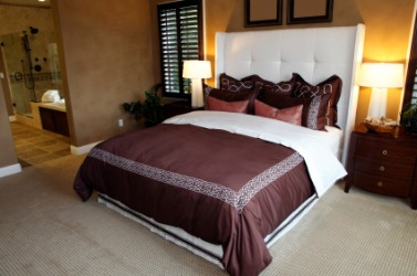 A bed with a brown and white bedspread.