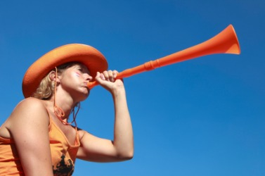 A young woman blows a vuvuzela.