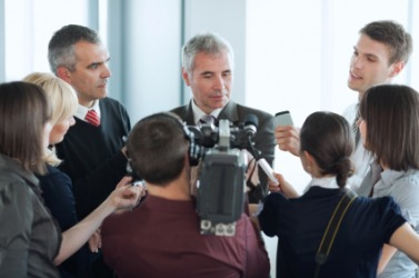 A man faces a barrage of reporters.