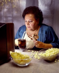 A woman binges on junk food and TV.