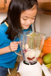 A girl blending ingredients to make a smoothie.