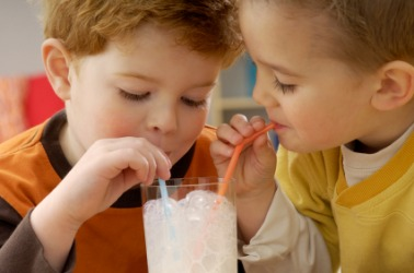 Two children bonding over a glass of milk.