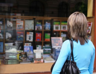 A woman looks into a bookstore window.