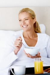 A woman enjoys breakfast in bed.