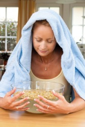 A woman breathes steam from a bowl.