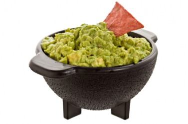 A bowl filled to the brim with guacamole.