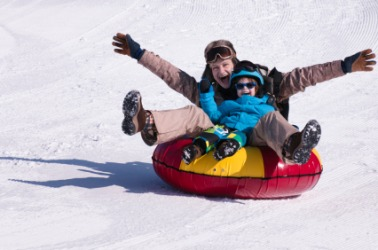 Two people careen down a snowy hill.