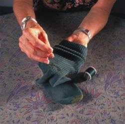 A woman darns a sock.