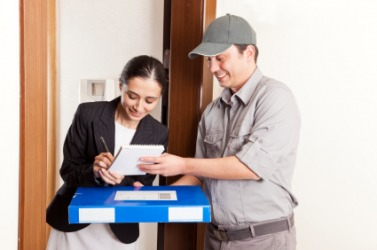 A woman accepts delivery of a package.
