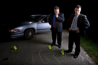 Two detectives investigate a murder scene.
