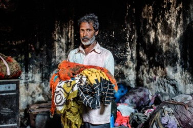 A dhobi with an arm full of laundry.