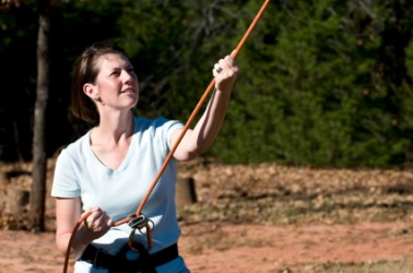 A woman belaying on a ropes course.